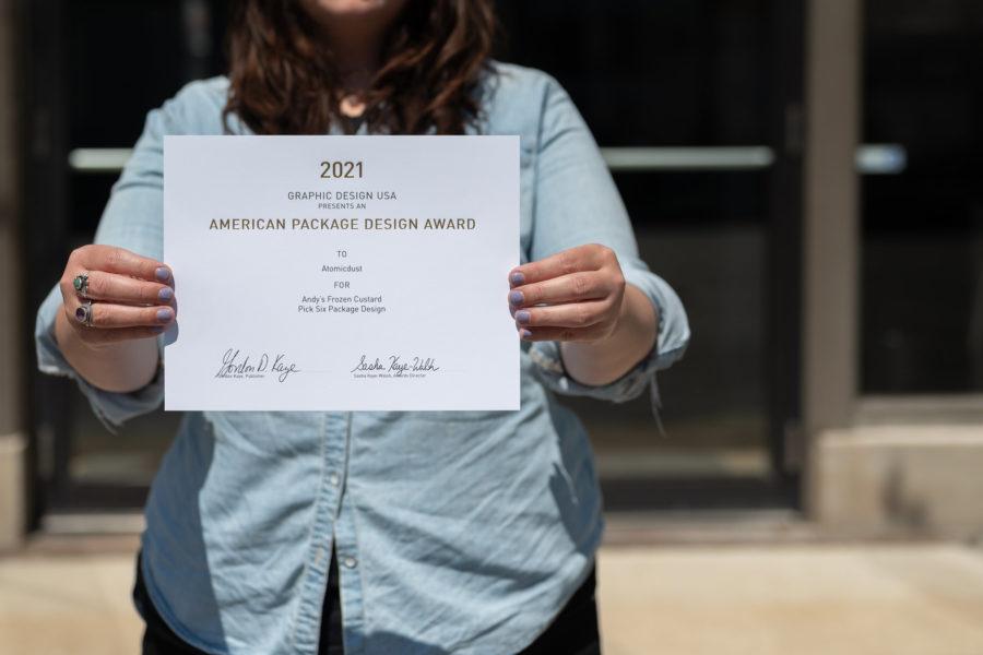 A team member holds the GDUSA Packaging Design Awards certificate