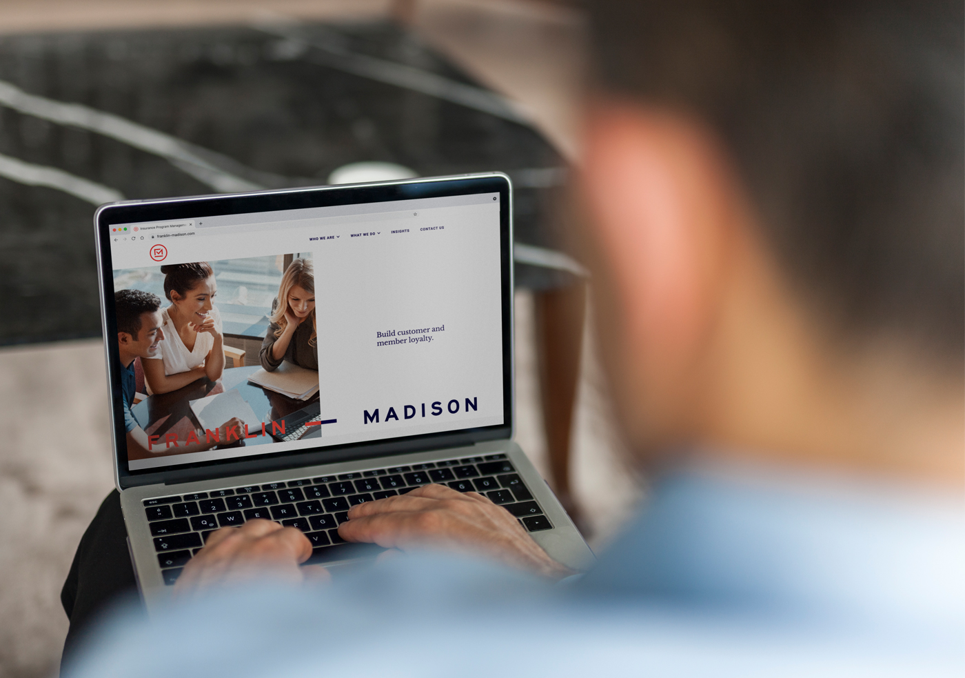 A person looks at the Franklin Madison B2B website design on a laptop