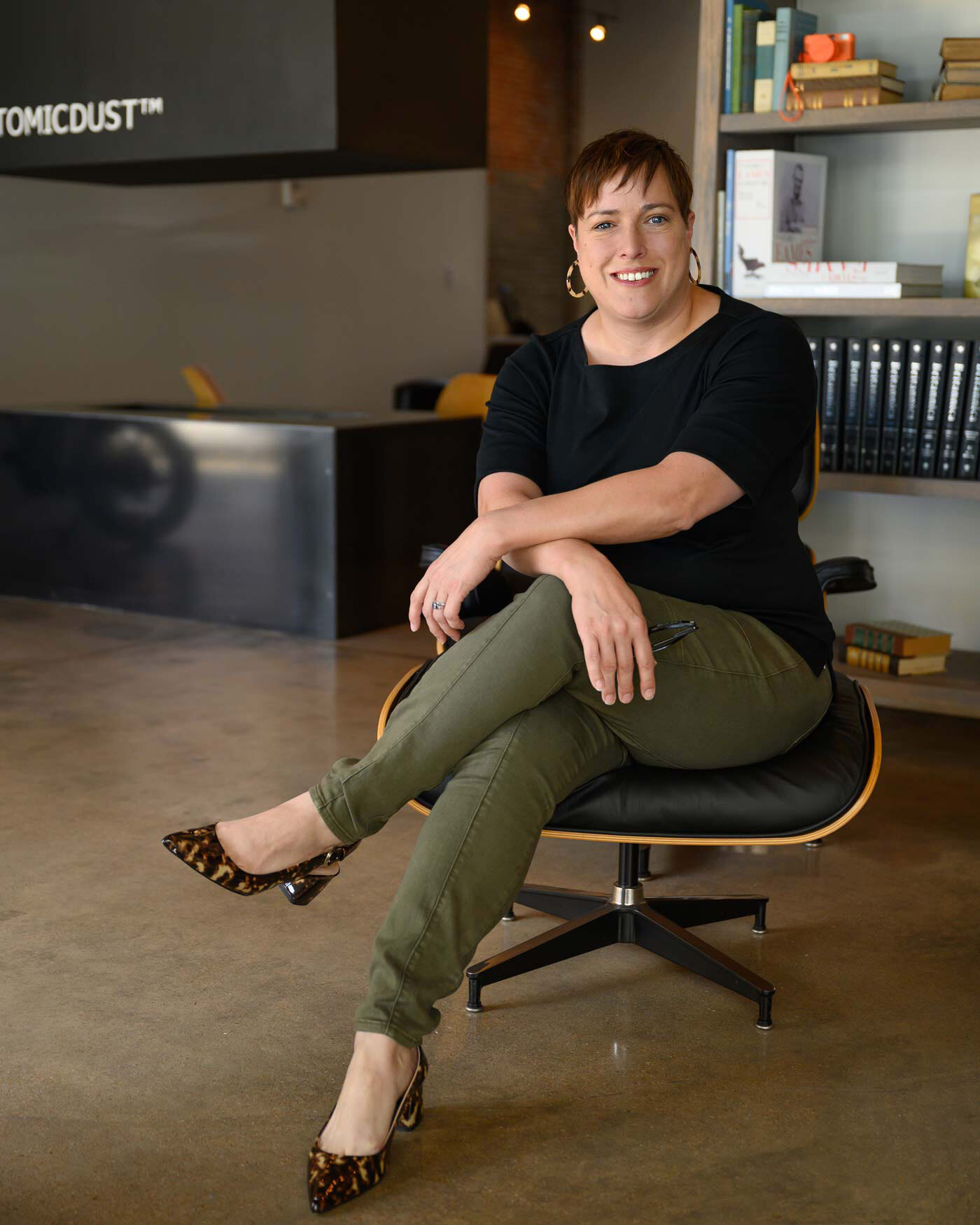 Holly Sinclair sits on an Eames chair in the Atomicdust office